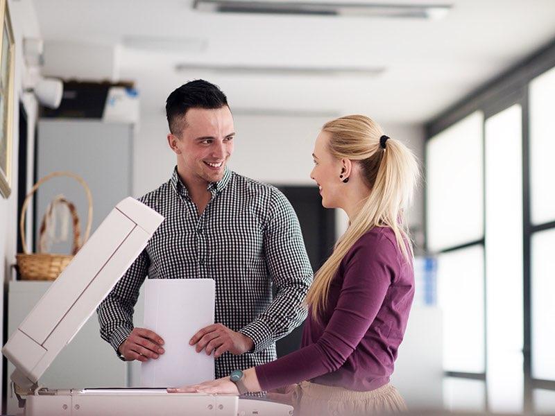 En man och en kvinna står och pratar vid en kopieringsmaskin.