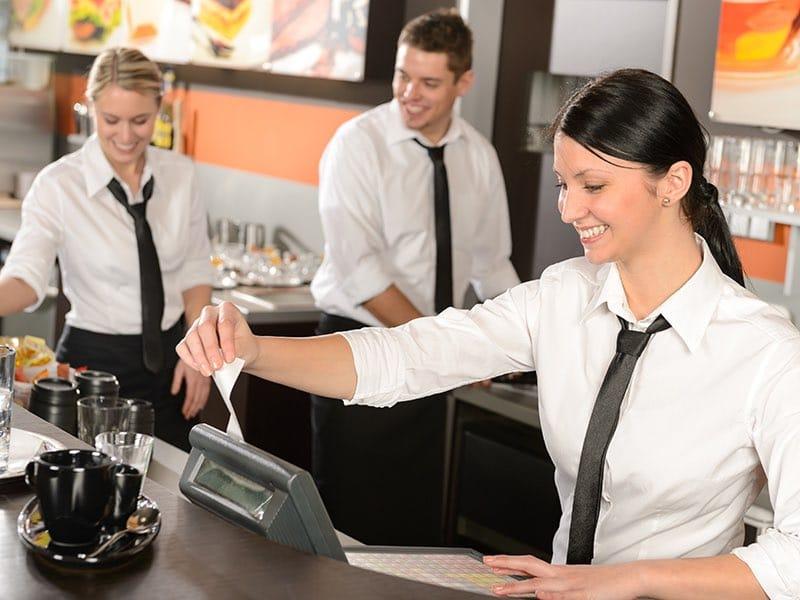 En kvinna slår in belopp i en kassa på ett café.