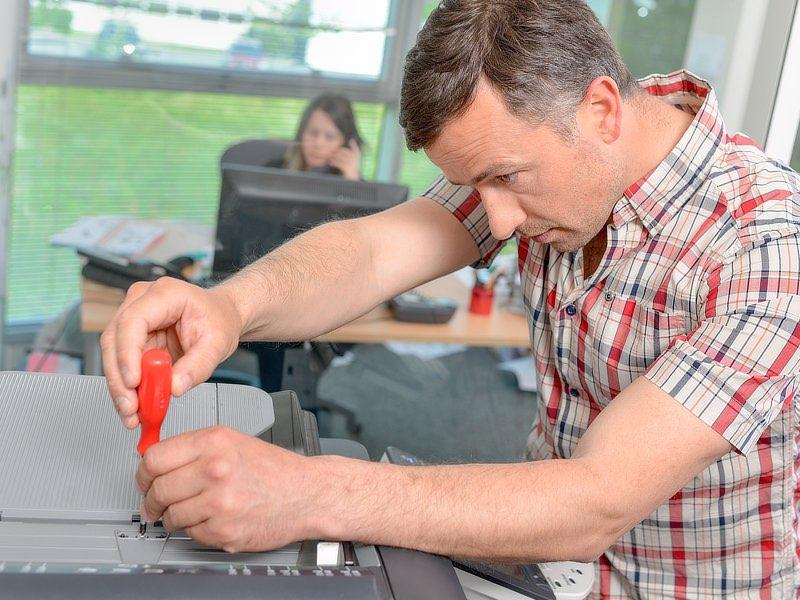 En tekniker reparerar en kopieringsmaskin.