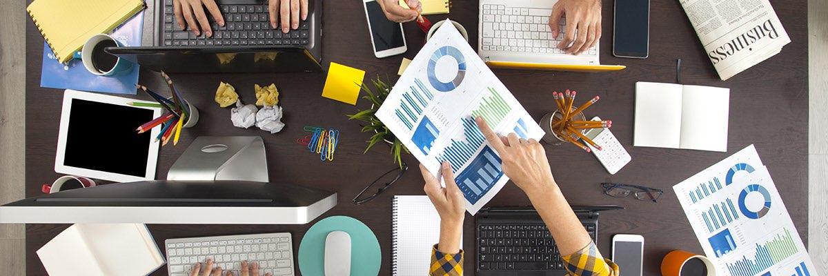 En grupp personer samlade runt ett skrivbord studerar ett affärsdokument.