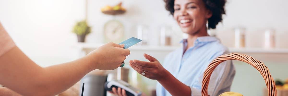 En person i en butik tar emot ett kreditkort för betalning.