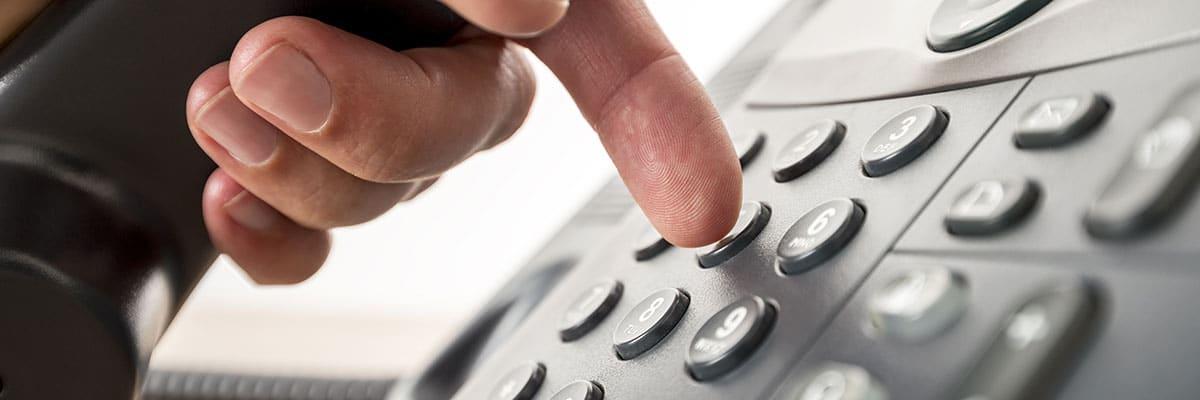 Närbild på en hand som skall slå ett telefonnummer.