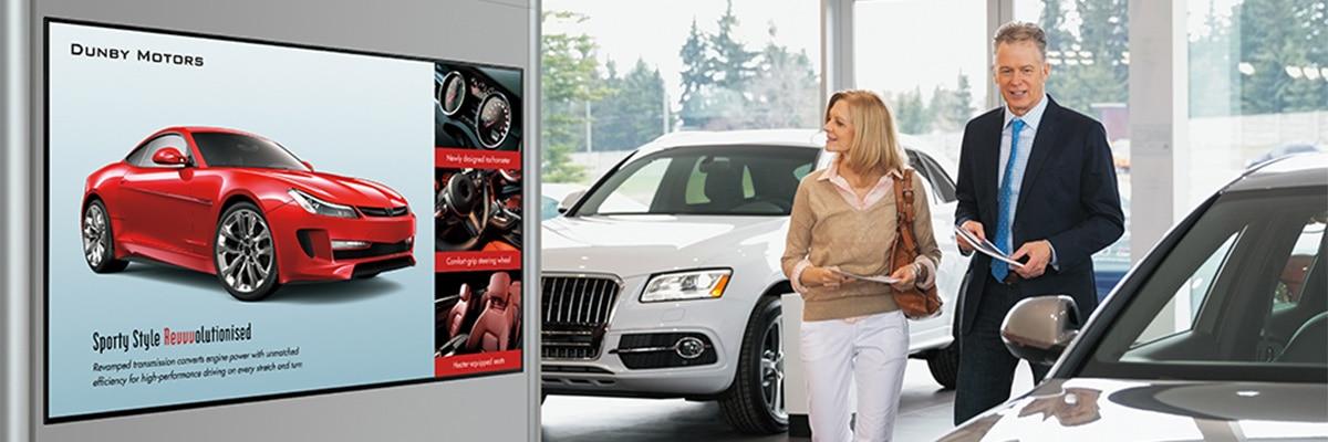 Ett medelålders par tittar på en storbildsskärm i en bilhall.