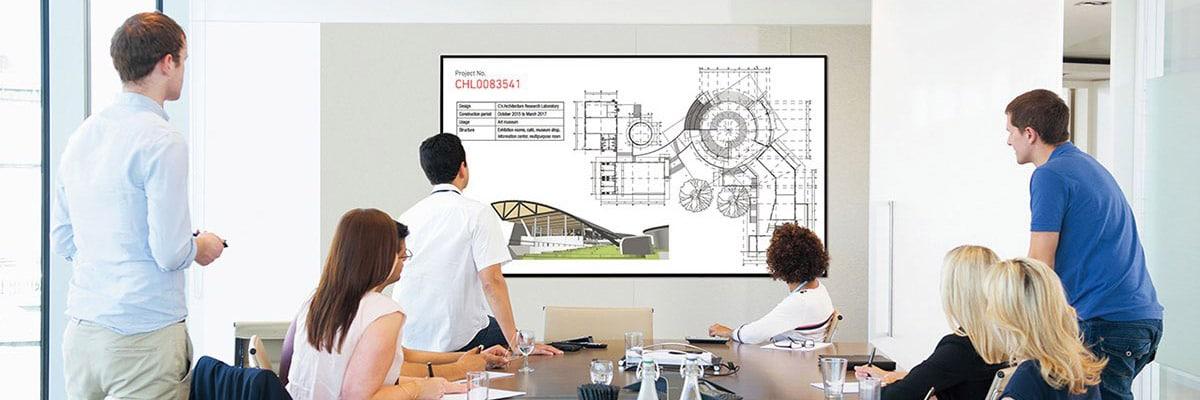 En grupp personer tittar på en storbildsskärm i ett konferensrum.