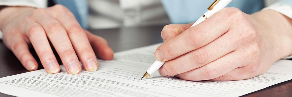 Närbild på en mans hand då han undertecknar ett avtal.